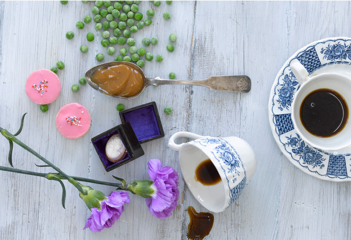 A spoon with fudge, some peas, flowers cups of coffee on the table