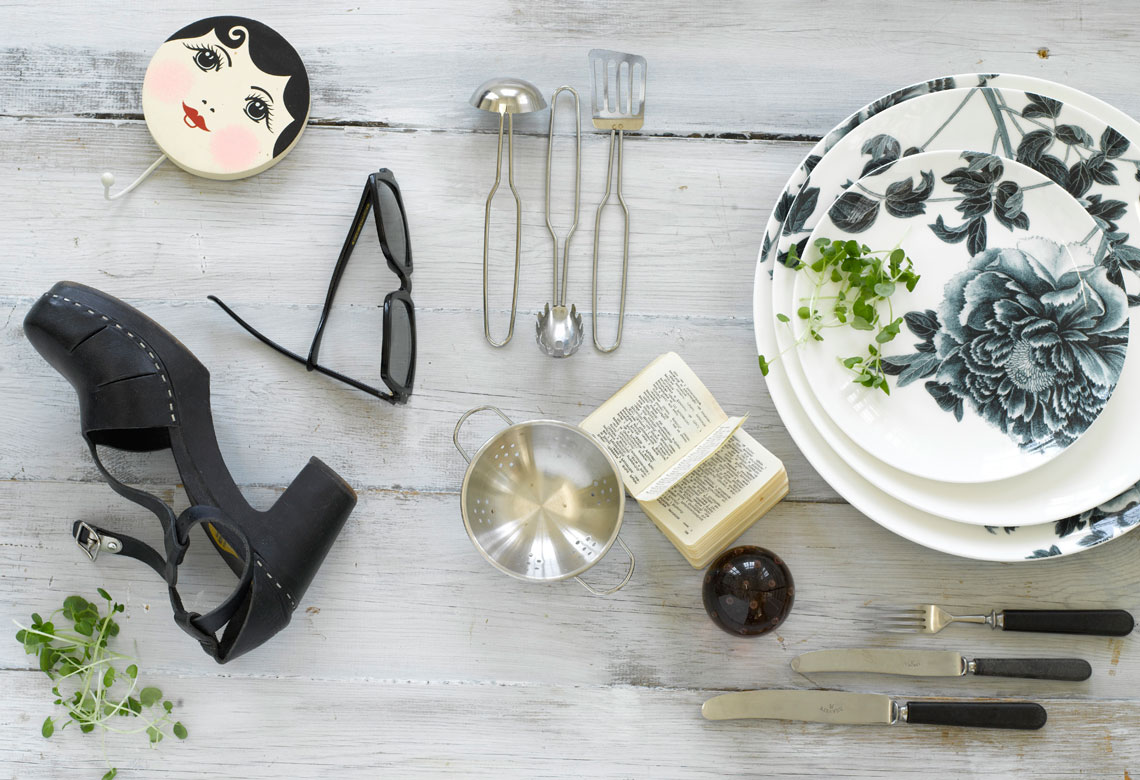 A shoe, sunglasses, utencils and plates on the table